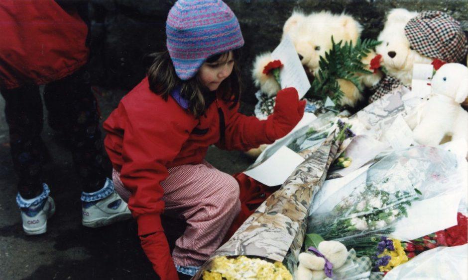 Abigail Longhurst lays flowers outside Dunblane Primary School.