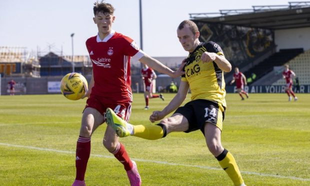 Aberdeen's Calvin Ramsay in action on his debut start against Dumbarton's Jaime Wilson in action.