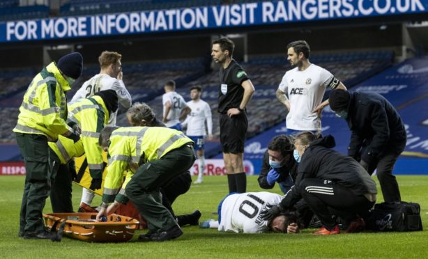 Cove Rangers midfielder Jamie Masson is stretchered off the field at Ibrox.