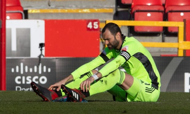 Aberdeen goalkeeper Joe Lewis is injured during the Scottish Cup tie against Livingston.