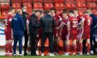 Aberdeen manager Stephen Glass talks to his players ahead of the penalty shoot-out against Livingston.
