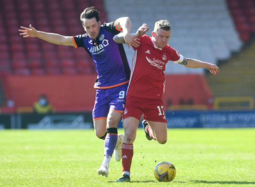 Jonny Hayes is put under pressure by Marc McNulty of Dundee United