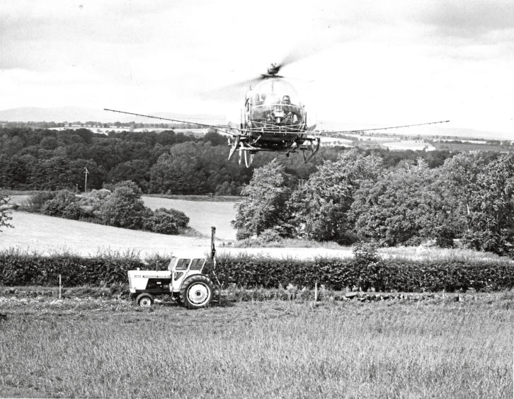 1979 - A helicopter sprays pea and bean crops at South Esk Estates, near Brechin