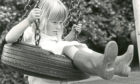 """1982 - Rebecca Linklater enjoys one of the rubber tyre swings at the Albury play park  13 August 1982  """"Rebecca Linklater on one of the tyre swings at Albury play area.""""  Used: EE 14/08/1982"""