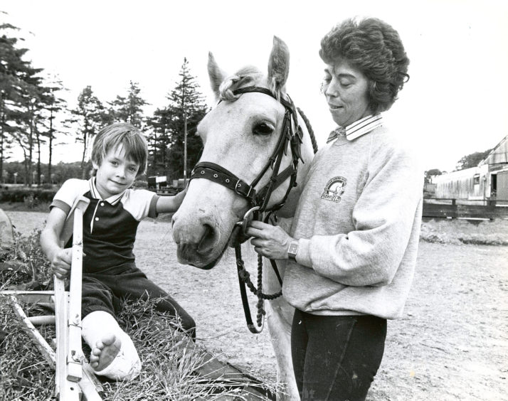 1990: Five year old Jeremy Harris, Aberdeen, who broke his leg on Sunday at an Inverurie play park, gives Fergus a playful pat under the watchful eye of Mrs Sue Crawford at Hayfield Riding Centre, Aberdeen.