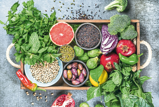 Vegetables, fruit, seeds, cereals, beans, spices, superfoods, herbs, condiment in wooden box for vegan, gluten free, allergy-friendly, clean eating and raw diet.