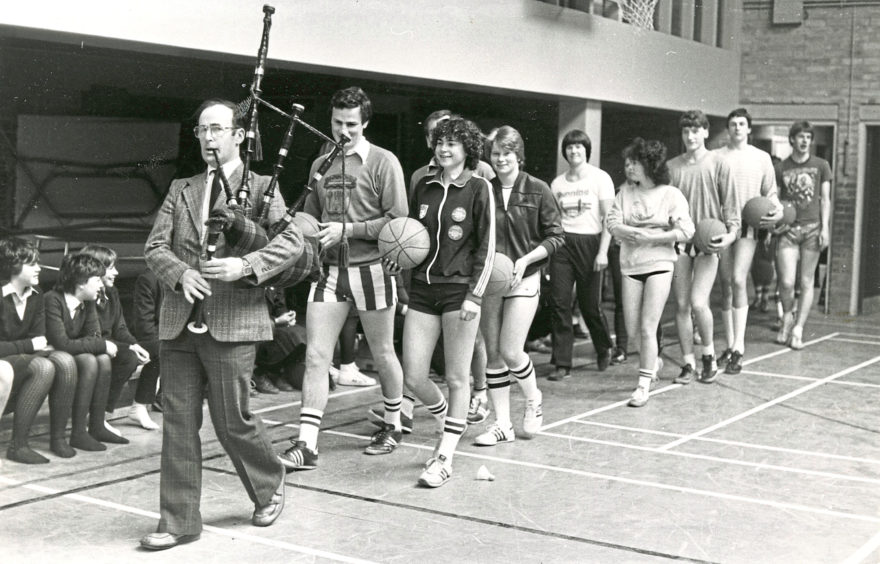 1983: These gladiators being piped into the arena by technical teacher Ron Gray are teachers and senior pupils who will take part in the IX Hazlehead Academy Lympic Games. The games opened with a basketball challenge. The staff won the match 18-16. The games go on all week with volleyball, water polo, hockey, football, table tennis, darts and badminton and the Lympic score to date stands at 5-3 for the pupils.