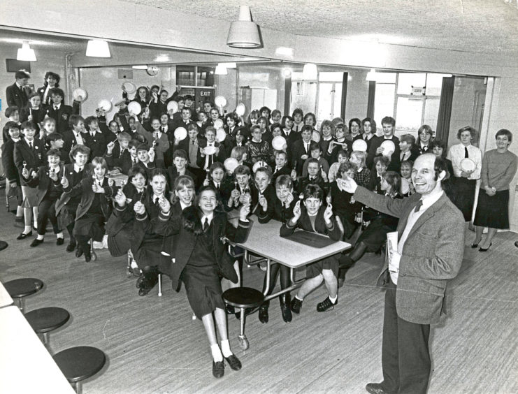 1987: Hazlehead Academy pupils raise empty plates in their dining hall to celebrate raising more than £1300 to help fill some plates through the Oxfam Hungry for Change sponsored fast. Oxfam district organiser Francis Johnson is pictured congratulations the 100 pupils who took part in the event with teacher Shelagh Bain who is also a member of the Oxfam Hungry for Change group.