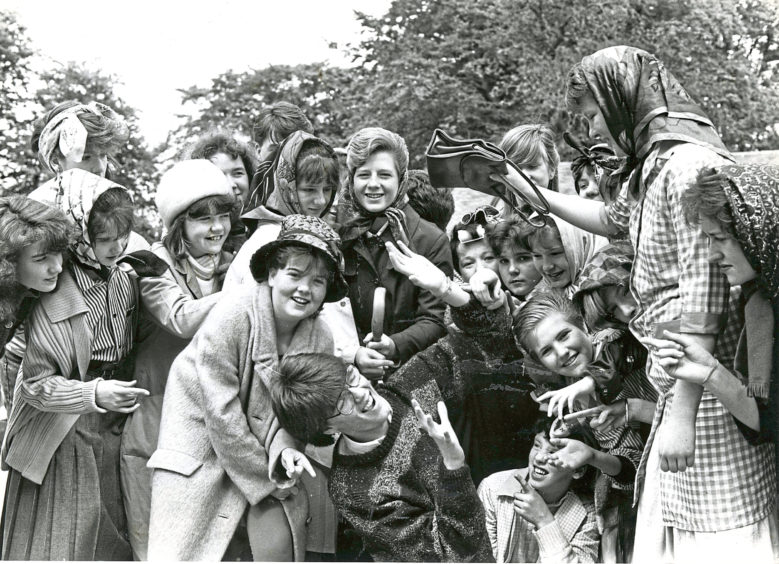1988: Hazlehead Academy's street theatre group go through their paces at Hazlehead Park in preparation for their performances of Wifies. Surrounded by wifies here is Lee Mundie (centre), who is taking a hammering from the handbag held by beverley Menmuir.
