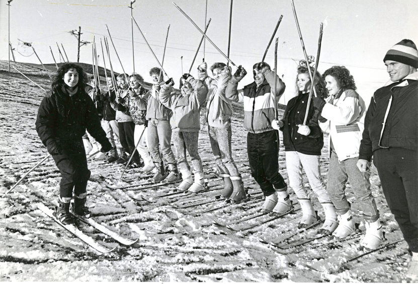 1988: Getting in the mood for their week's skiing holiday in Schaldimg, Austria, are these 5th year and 6th year pupils at Hazlehead Academy, Aberdeen. Here Jayne Anderson gets a cheer as she sails down the snow covered slope. Physical education teacher Mr Victor Burnett (fourth right) will accompany the skiing party to Austria.