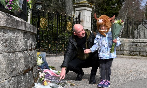Floral tributes left at the Balmoral Castle front gate in memory of the late Duke of Edinburgh, Prince Philip. Pictured are Steve Mitchell and daughter Constance, 4.