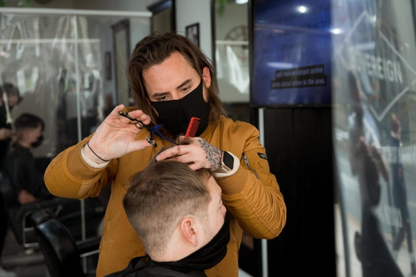 Kyle Ross cuts a customer's hair on Monday as barbers reopen for business