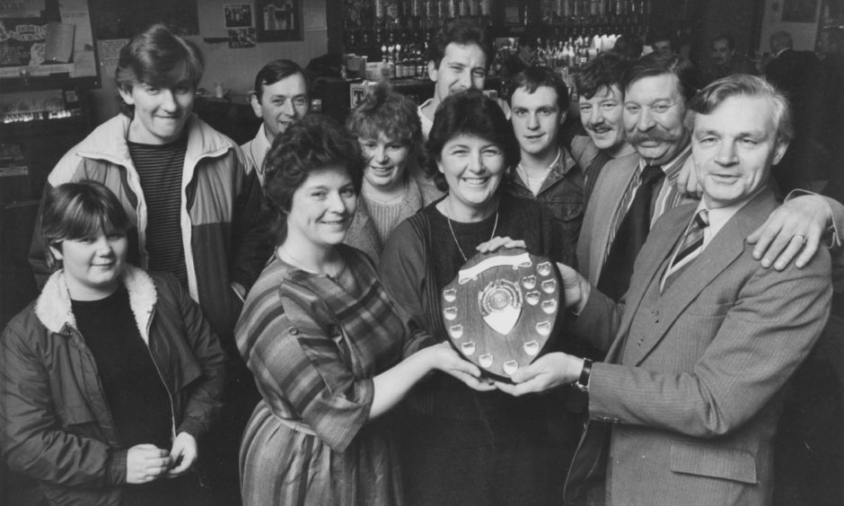 The Lord Byron Bar at Northfield won the Royal National Institute for the Blind competition for the biggest pile of pennies to be collected for institute funds in 1984. Bar staff Norah Gribble and Georgie Boyle were presented with the Andy Stewart Shield watched by bar manager Sandy Cruickshank and customers.