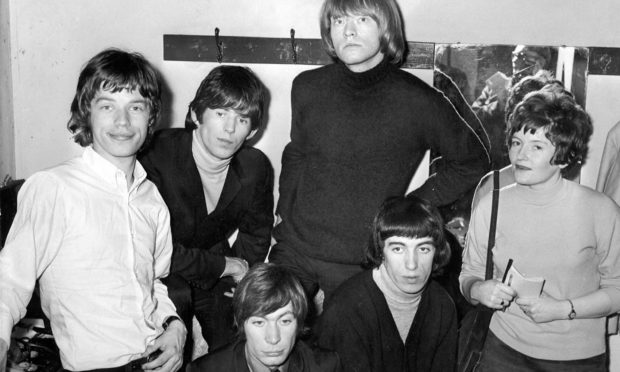 The Rolling Stones - Mick Jagger, Keith Richard, Charlie Watts, Brian Jones, and Bill Wyman - with reporter Julie Davidson before their gig at the Capitol in  1965.