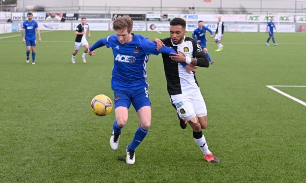Cove Rangers midfielder Blair Yule holds off Dumbarton defender Rico Quitongo.