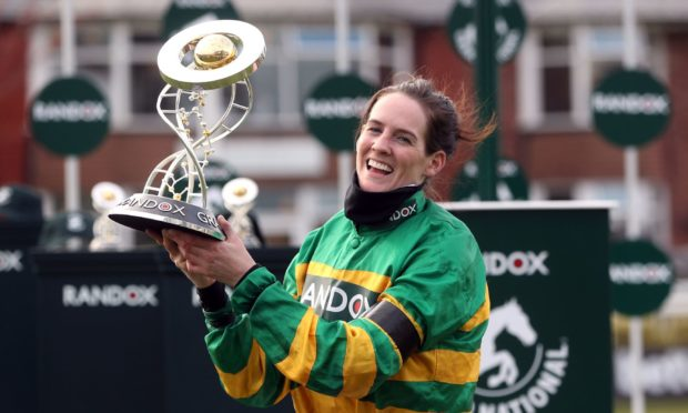 Jockey Rachael Blackmore receives the Randox Grand National Handicap Chase trophy.