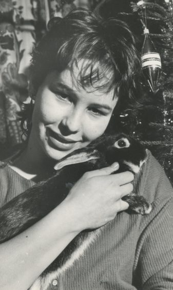 """1984 - Jane Mackie (pictured) You will have undoubtedly heard the story of the black sheep, and you will probably also be aware of the advantages of meeting a black cat on your travels. But now we can reveal the sorry tale of the missing black rabbit found only days ago roaming the streets of Aberdeen. Medical student Jane Mackie, said last night: """"My dad and our neighbour Mrs Eleanor Ewen saw him on the street last Thursday and he ran under our car. But they managed to get him out, and we've had him in our house ever since. Our tropical fish don't mind at all, but the family cat Smokey, has had to be kept away from him, because he doesn't know what a rabbit is, and we fear the worst."""" Jane and the rest of the family have since checked with their neighbours and friends who own pet bunnies, but without finding this one's master or mistress. The mystery itinerant is described as either black or very dark brown with lighter brown paws and a light patch behind the ears."""""""