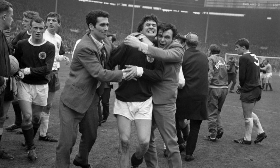 Jim Baxter was hugged by fans after Scotland's 3-2 win at Wembley in 1967.
