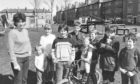 1984 - Mrs Moira McLennan with her son Bruce (13) (fourth from left), and several of the neighbours  children who would use a play area if the council agreed to building one in the background.
