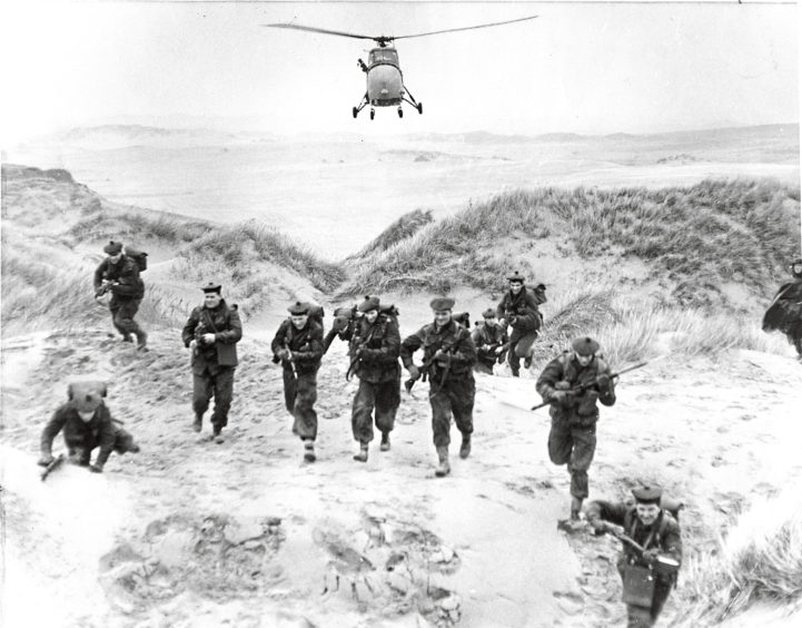 1966: An enemy's-eye view of TA Gordons on the attack, with close support from a low-flying Navy helicopter during an exercise for men of Headquarters Company, 3rd Battalion the Gordon Highlanders, at Black Dog, Aberdeen, at the weekend.