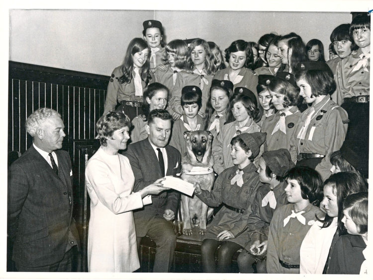 1970: Members of the 37th and 37th A Brownies, Guides and Rangers, Beechgrove Church, Aberdeen, look on as Brownie Janet Stewart, presents a cheque to Mr Alex Duguid, Guide Dogs for the Blind Association, at a ceremony in the church hall last night. With Mr Duguid is Pearl Murray, the Press and Journal woman's editor. The 37th are the first of the city Guides to reach their guide dog target. One of their group Jill Porteous, will take delivery soon of a puppy to be reared at her home before undergoing guide dog training. The puppy will be known as Diamond.