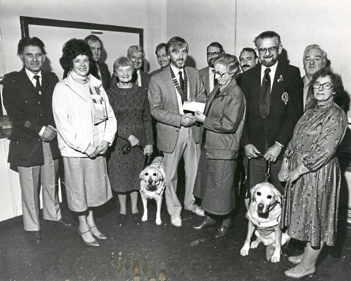 1984: £1000 boost was put into the coffers of the Guide Dogs for the Blind last night, thanks to the efforts of schoolchildren in Grampian who raised cash in a sponsored football competition. More than £3000 was raised during the event which is organised annually by Bucksburn and District Round Table. Aberdeen branch chairman Mrs Sally Leiper (centre) accepts the £1000 cheque from Buchan Tablers chairman Mr John Leheny. The presentation took place after the branch annual meeting. Also pictured are members of the Round Table and commitee members of the Guide Dogs for the Blind branch including Miss Isobel Mundie (left) and her dog, Unity, and (right) Mr Jack Smith with Victor.