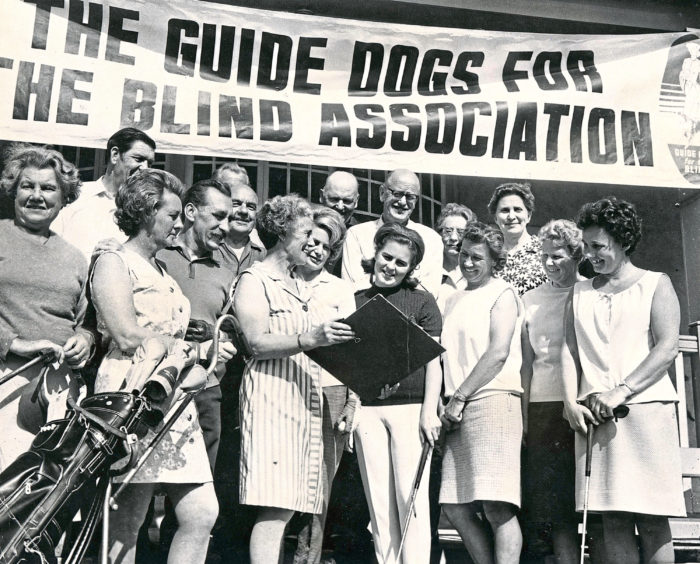 """1970: The golf course at Hazlehead was the scene of a hard hitting bid to raise money to buy guide dogs for the blind. In our picture, Mrs D. M. Godsman shows competitors their starting times at the start of the mixed foursomes, in aid of Guide Dogs for the Blind Association, Aberdeen branch. Well known Aberdeen player Mrs Joan Rennie (dark sweater) looks on."""""""
