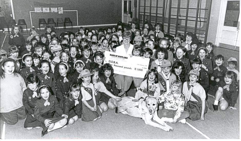 1991: Guides and Brownies of the Parkway District of Aberdeen Guides had a fundraising drive during which they raised £1,000 for the Guide Dogs for the Blind Association. All the fundraisers gathered in Westfield Primary School, Bridge of Don, to present the cheque to Mrs Nessie Fraser and her guide dog, Norman.