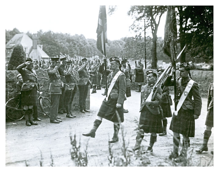 1939: Colours of the 5th Gordons Highlanders being escorted off for safe custody.