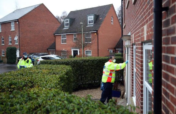 A Community safety patrol officer knocks on the door of a resident in Bramley Green, Hampshire, during a surge testing programme after a case of the South African variant of Covid-19 was identified in the village. Picture date: Wednesday February 17, 2021.