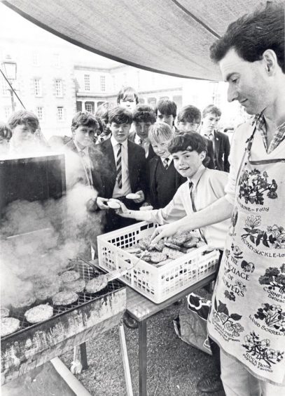 English teacher Michael Duncan and pupil Gregor Maxwell serve up some burgers to a group of hungry students at a barbecue