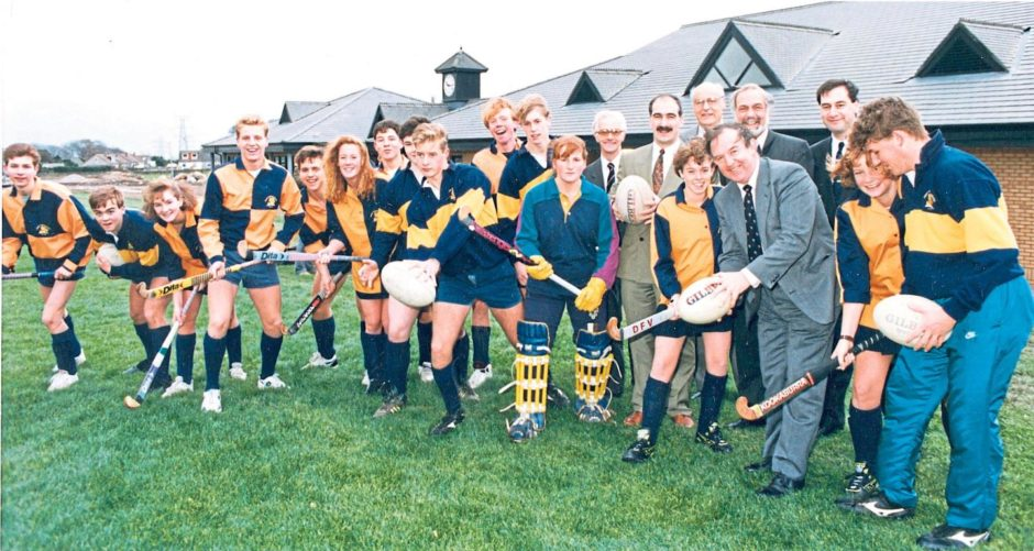 Headmaster George Allan joins hockey and rugby players ready to try out the new £3 million sports field development at Countesswells