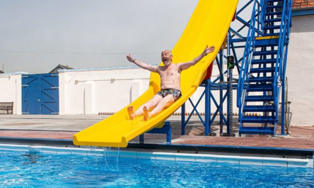 Friends of Stonehaven Open Air swimming pool group's chairman Pete Hill speed testing the new chute at the grand reopening