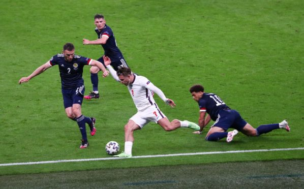 Scotland players close down England midfielder Jack Grealish.
