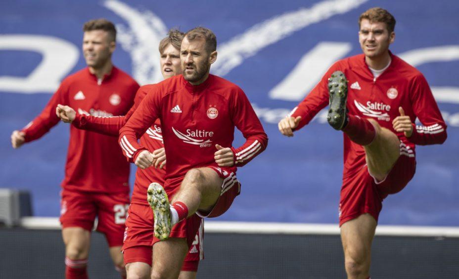 Niall McGinn, centre, warms up against Rangers.