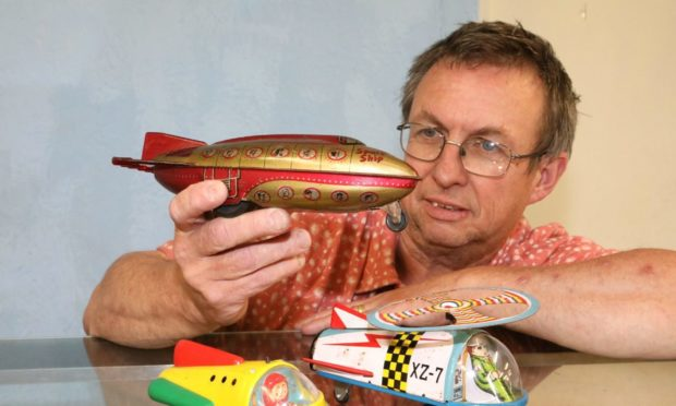 Dave Smith of Bervie Auctions in Inverbervie with tin plate1950s space rockets