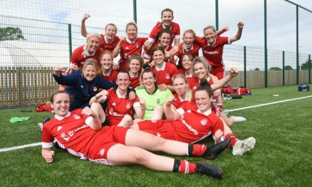 The Aberdeen FC Women squad celebrate after winning the title at Dundee United