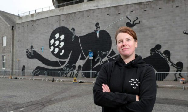 Artist KMG (Katie Guthrie) pictured with her striking mural on Palmerston Road