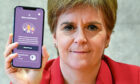 First Minister Nicola Sturgeon views the new Covid-19 track and trace app on a phone at the Scottish Parliament in Edinburgh.