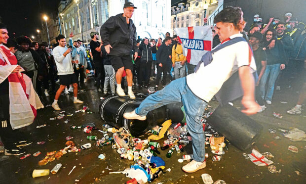 English fans kick and stand on a litter bin in Piccadilly Circus, London, after Italy beat England on penalties to win the UEFA Euro 2020 Final. Picture date: Monday July 12, 2021.