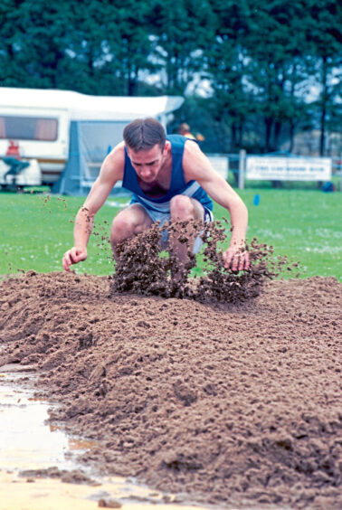 1998 - A long jump competitor lands in the sand at the 1998 Stonehaven Highland Games