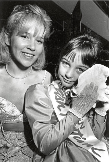 1990 - Listening for the sound of the sea in a big  shell is 10-year-old festival princess Danielle  Maloney, with mermaid Yvonne Collins