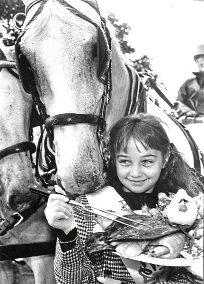 1990 - Jan the horse gets a noseful as ten-year-old  Festival Princess Danielle Maloney opens  the 7th Aberdeen Fish Festival with a fish  breakfast at the Caledonian Hotel