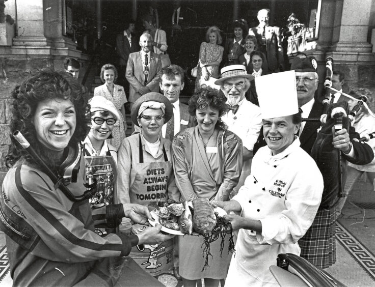 1989 - 'Deep sea diver' Geo Mitchell hands over the fish  for the breakfast to launch the Aberdeen Fish Festival  Week at the Caledonian Hotel, Aberdeen, to head chef  Brian Mutch