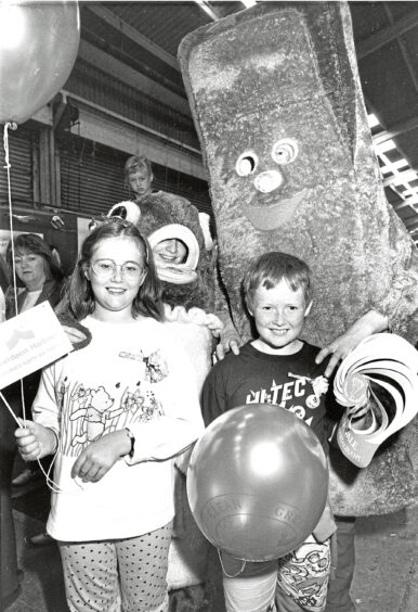 1990 - Harry Haddock and Charlie Chip say hello to  Kirriemuir siblings Fiona, 11, and David Glen,  8, who were visiting the fish festival