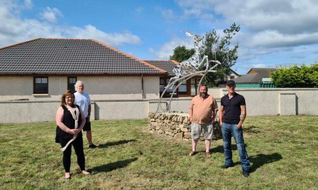 Artist and creator Carn Standing unveiling the statue alongside councillor Sonya Warren; councillor David Bremner and Paul Bigl, Stonemason