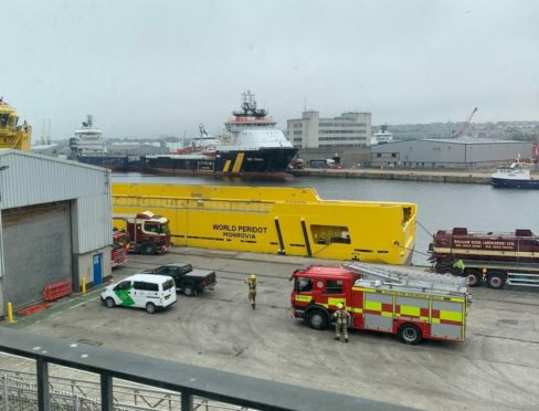 Firefighters are currently working to free a man from a confirmed space onboard an American offshore supply vessel.