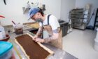 Pete Leonard prepares cinnamon buns for another busy day ahead at Bandit Bakery in Rose Street, Aberdeen.
