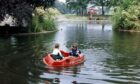 Two young boys enjoy the fine October weather by playing in one of the pedalos on the duck pond at the Duthie Park in 1990.