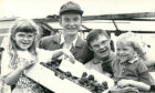 1992 - A barbecue and barn dance held by  Strichen farmer Gammack Coutts and his  wife, Moira, raised £1,121 for Easter  Anguston Farm where their son, Russell,  19, is a trainee. David Walker, second  left, and Russell accept the cheque from  Russell's siblings Claire and Clark